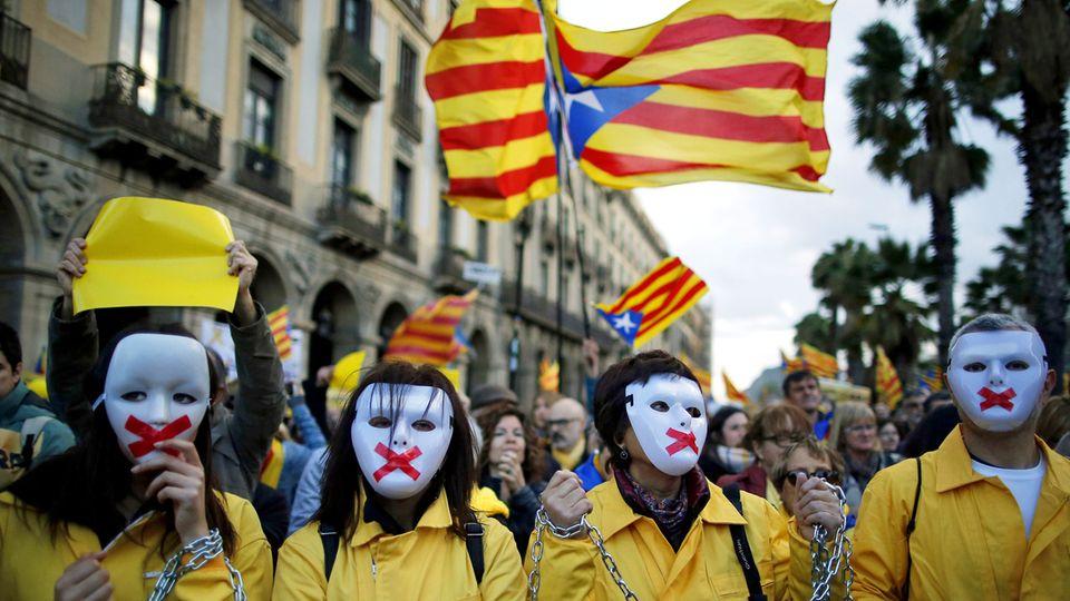 Proteste in Barcelona: Demonstranten mit Masken und verketteten Händen nehmen an einer Demonstration vor hochgehaltenen Esteladas, der Unabhängigkeitsflagge Kataloniens, teil.