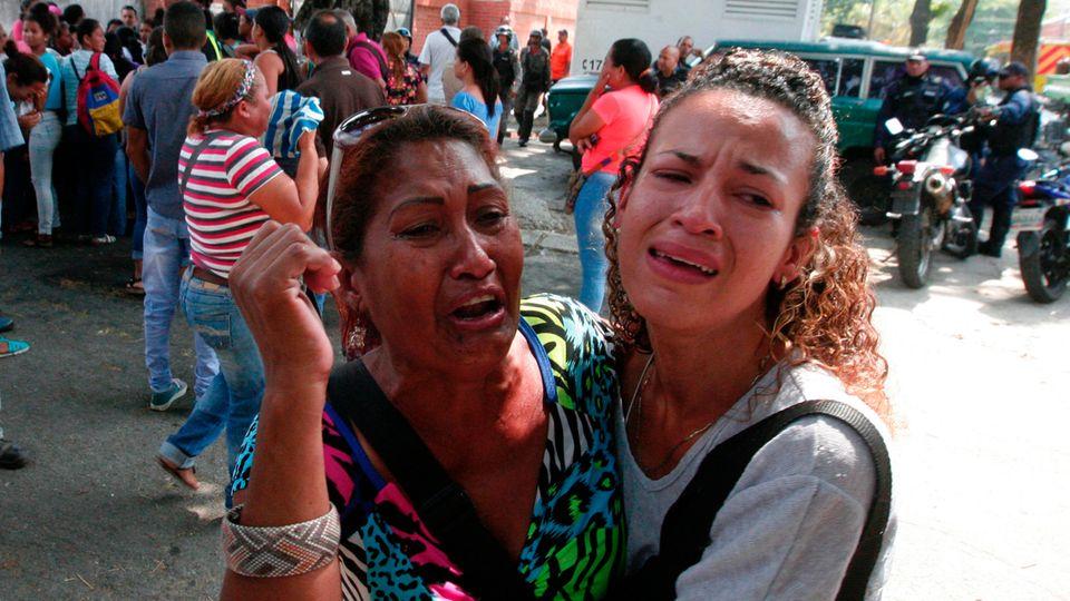 Angehörige der Häftlinge trauern vor einer Polizeistation in Venezuela