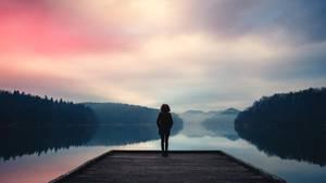 Eine Frau steht an einem See und blickt in die Ferne