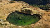 Zwei Wanderer sehen beim Abstieg vom Ramolhaus in den Ötztaler Alpen einem klaren Grün ins Auge.