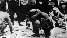 In Wien amüsieren sich Mitglieder der NSDAP über ältere Juden, die den Bürgersteig mit Bürsten schrubben müssen