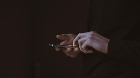 USA – ein Mann hält ein Handy in der Hand