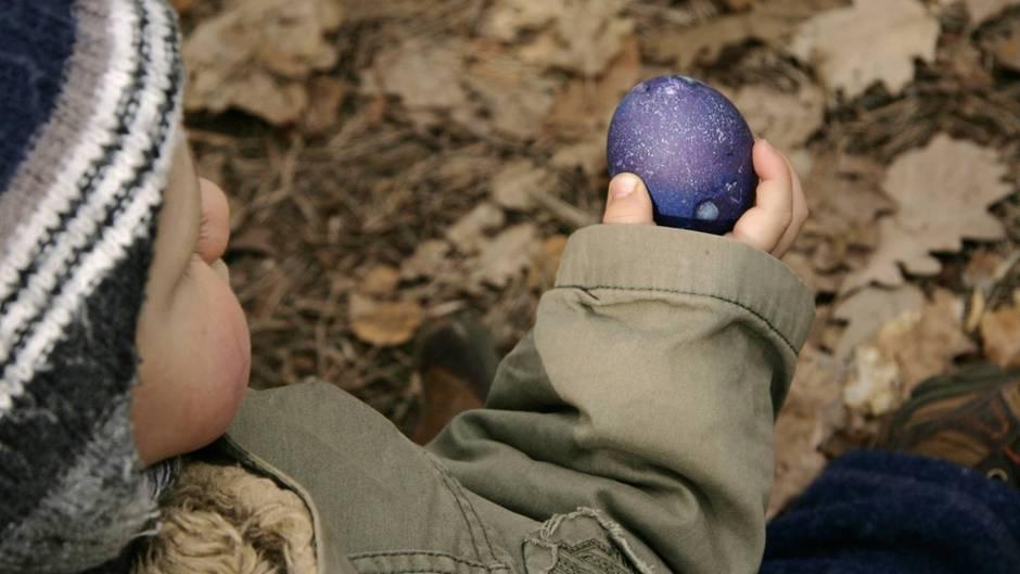 Ein Junge in Winterkleidung hält ein Osterei
