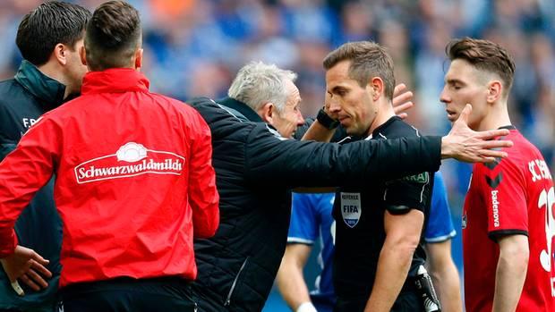 Freiburgs Trainer Christian Streich redet wegen der Gelb-Roten Karte für Nils Petersen auf Schiedsrichter Tobias Stieler ein