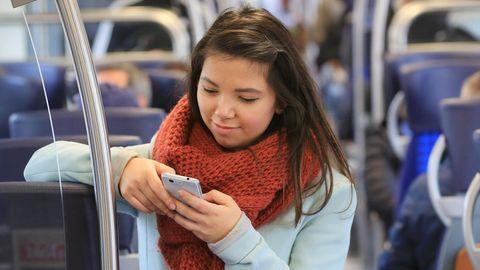 Eine junge Frau tippt in der Bahn auf ihrem Smartphone