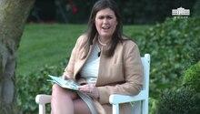 Sarah Huckabee Sanders sitzt auf einem weißen Gartenstuhl im Garten des Weißen Hauses. Auf dem Schoß hat sie ein Kinderbuch.