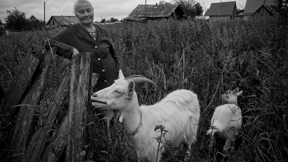 Das ist Großmutter Tamara, eine Bewohnerin des DorfesMozarka. Sie lebt allein als Bäuerin. Ganz besonders stolz ist sie auf ihre Ziegen, Hühner, Truthähne und Katzen. Aufopfernd kümmert sie sich um die Tiere, bereitet ihnen Futter und zerkleinert Brennholz.