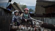 Die Jungen aus den Dörfern werden schon früh in die Hausarbeit eingebunden. In spielerischer Form folgen sie den Anweisungen der Eltern. Im Auftrag, das Holz für den Winter vorzubereiten, setzten sich die Jungs lachend Helme auf und posieren für ein Foto.