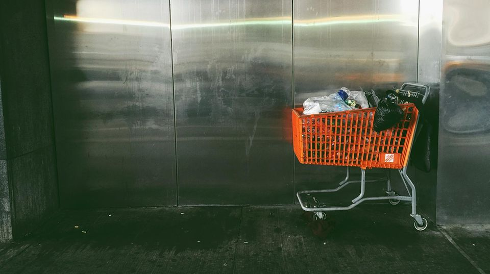 Oranger Einkaufswagen mit Müll gefüllt