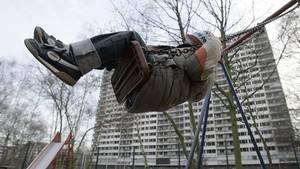 Grundsicherung und Hartz IV in Familien mit Kindern. Ein Kind schaukelt auf einem Spielplatz vor einer Hochhaussiedlung.