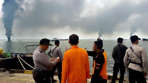 Menschen sehen vom Hafen in Balikpapan, Borneo, auf den Ölteppich im Meer. Rauch steigt auf.