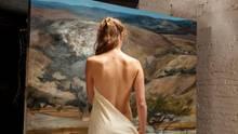 Eine unbekleidete Frau steht vor einem Gemälde