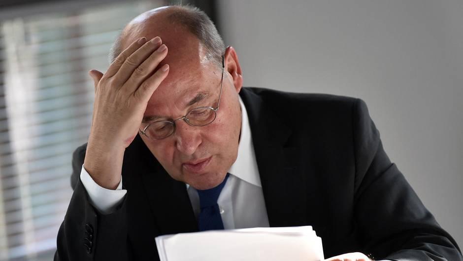 Gregor Gysi sitzt an einem Tisch und blättert in Papieren