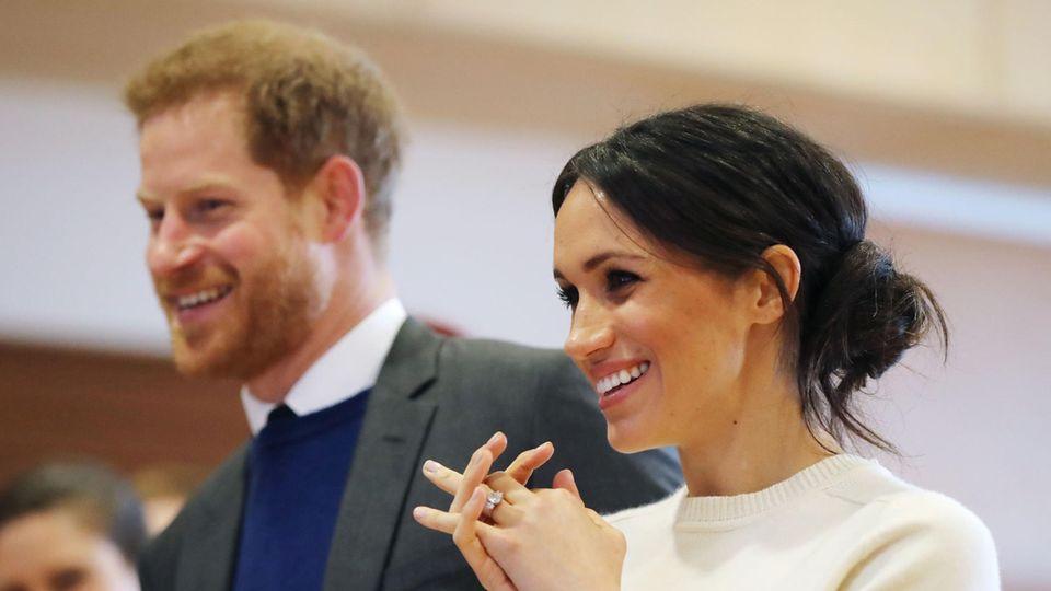 Megah Markle steht im weißen Wollpulli neben Prinz Harry und lächelt