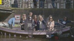 Von einem Boot aus fischen Frauen mit Keschern Plastikmüll aus einer Gracht in Amsterdam