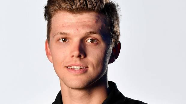 Michael Goolaerts, eine junger Mann mit dunkelblondem Seitenscheitel und braunen Augen, steht im schwarzen Team-Shirt im Studio