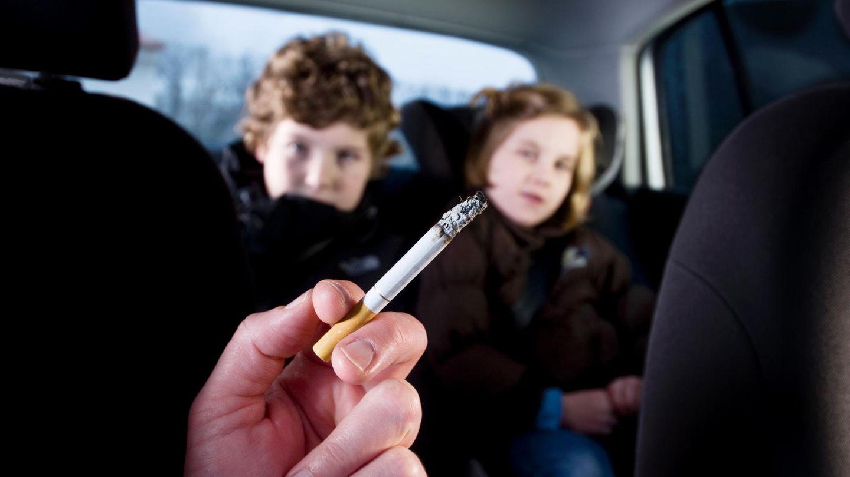 Rauchender Erwachsener mit Kindern im Auto