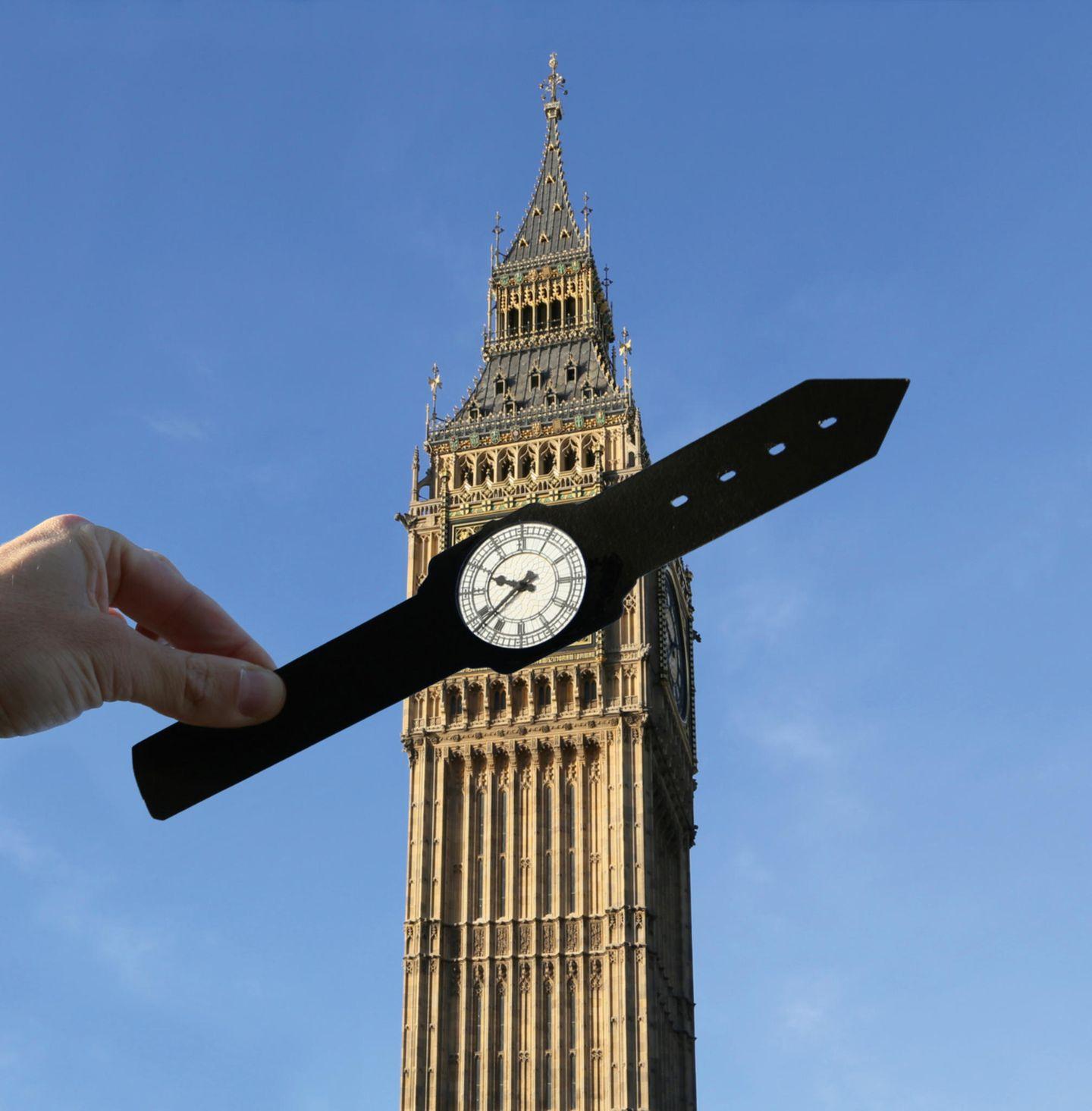 Der Fotograf hält ein Armband einer Uhr so vor den Big Ben, dass er aussieht wie eine Armbanduhr