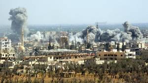 Syrien, Region Damaskus: Rauch steigt nach dem Einschlag einer Rakete der syrischen Armee über Duma auf.