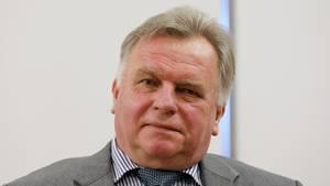 Günther Krause, ein Mann mit grauem Seitenscheitel, sitzt in grauem Anzug, blau-weiß gestreiftem Hemd und Krawatte am Tisch