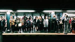 Menschen an Ubahnstation gucken aufs Handy