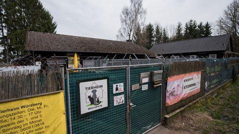 Hinter einem mit Planen verhängten mannshohen Metalltor sind die Dächer zweier Gebäude zu sehen, die im rechten Winkel stehen