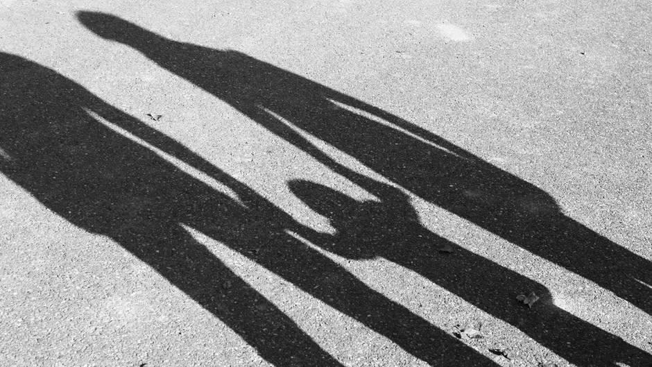 Freiburger Missbrauchsfall: Schatten eines Kindes zwischen zwei Erwachsenen