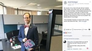 Mann in einem Büro, er trägt Anzug und Fliege und hält die Lunchbox mit Katzen darauf in der Hand
