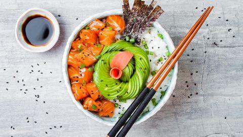 In dieser Schüssel befindet sich Lachs-Poke mit Algenblättern, Avocado, Sesam, Frühlingszwiebeln und Reis.