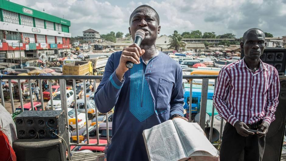 Ein Mann steht mit Mikrofon in der rechten und Bibel in der linken Hand auf dem größten Marktplatz in Accra.