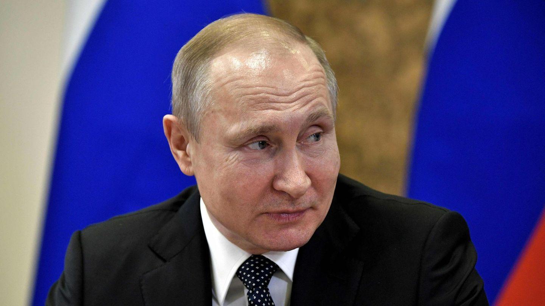 Mit einer russischen Flagge im Hintergrund sitzt Wladimir Putin an einem Tisch und schaut lächelnd zur Seite