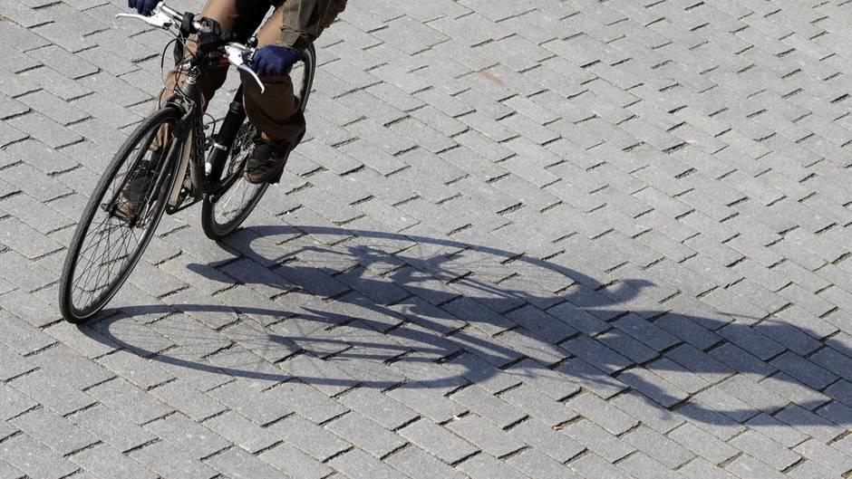 Ein Radfahrer fährt mit Schwung eine Kurve und wirft dabei einen langen Schatten auf graues Straßenpflaster