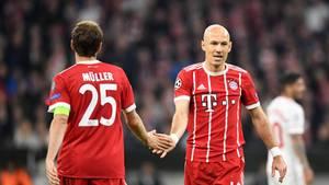 Thomas Müller und Arjen Robben vom FC Bayern München klatschen im Vorübergehen ab
