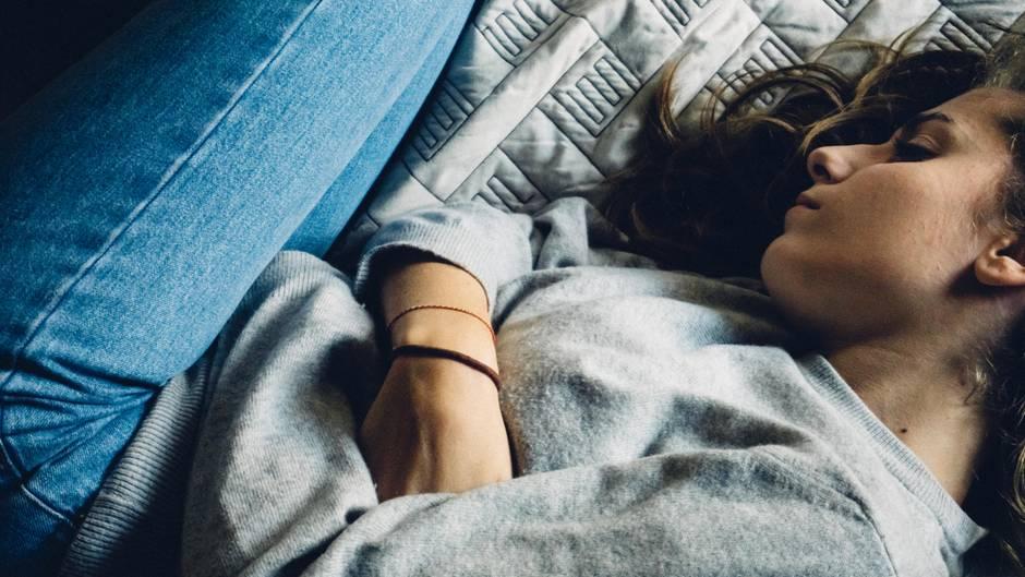 Eine junge Frau liegt auf einem Bett