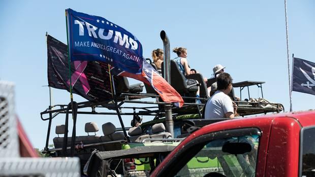 Nicht nur Banales im Schilde: Neben einer Trump-Wahlkampf-Fahne flattert das pinkfarbene Symbol des Kampfes gegen Brustkrebs
