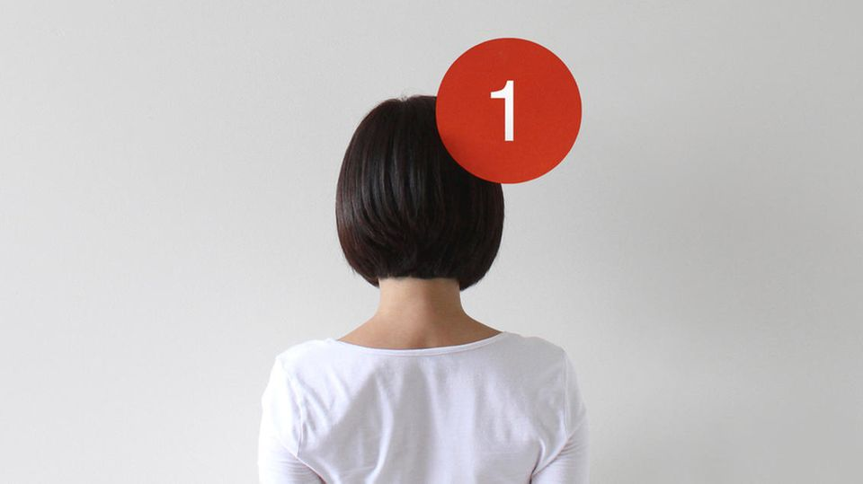 Eine Frau mit dem Rücken zur Kamera und einem Notification-Bubble am Kopf