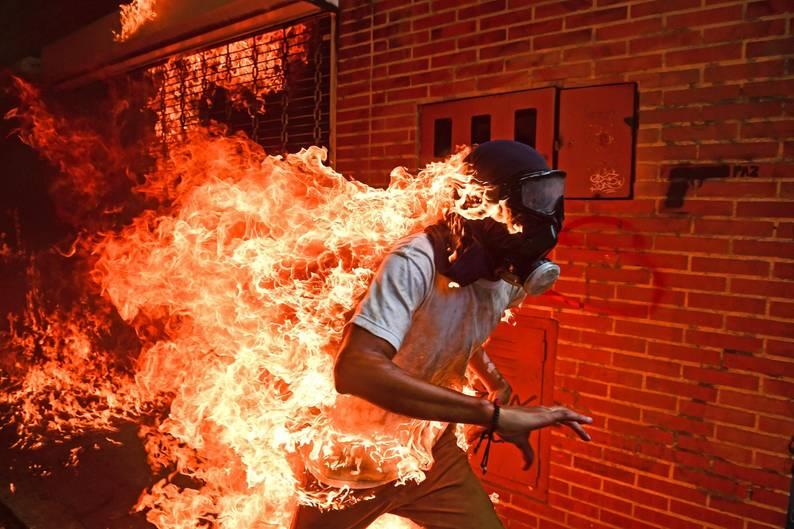 """""""Venezuela Krise"""" lautet der schlichte Titel des spektakulären Fotos, mit dem der Fotograf Ronaldo Schemidt jetzt den Titel für das Weltpressefoto des Jahres gewann. Das Bild zeigt den Demonstranten José Víctor Salazar Balza, der während der Proteste gegen Venezuelas Präsident Nicolás Maduro im Mai 2017 von Flammen erfasst worden war. Er überlebte mit schweren Brandwunden"""