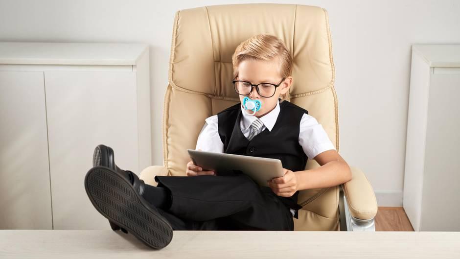Ein Junge sitzt in einem Chefsessel und liest – mit Schnuller im Mund