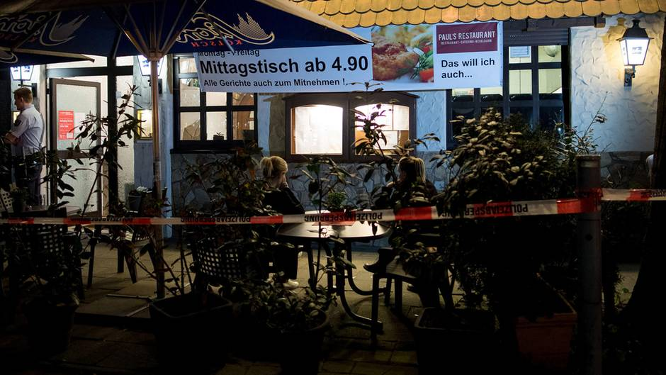 Köln: Polizisten stehen vor einem Restaurant. Im Keller hat die Polizei zwei Leichen gefunden.