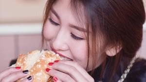 Eine Asiatin beißt in einen Hamburger