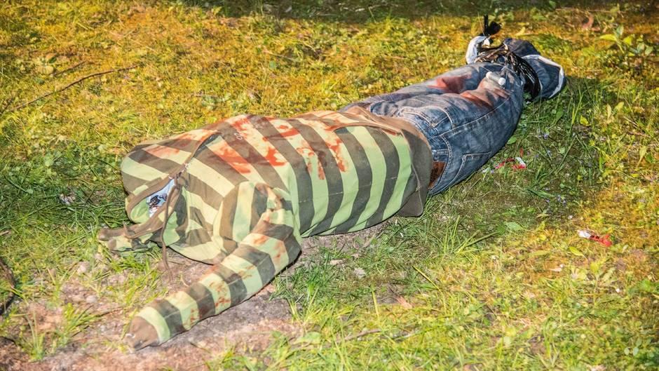 Eine kopflose Puppe in gestreiftem T Shirt und Jeans gekleidet auf Gras- Die Puppe war Anlass für einen Polizei-Einsatz