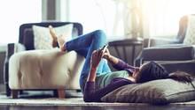 Eine Frau liegt auf einem Kissen und guckt auf ihr Smartphone