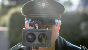 Blitzer in Deutschland: Ein Polizist misst an einer Kontrollstelle der Polizei