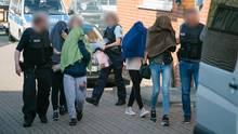 Beamte der Bundespolizei eskortieren Fraen aus einem Gebäude