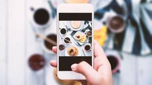 Jemand fotografiert essen mit dem Handy