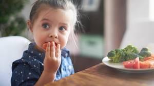 Ein Mädchen isst Gemüse