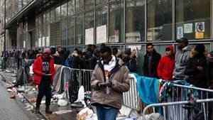 Geflüchtete stehen in Paris Schlange, um Asyl zu beantragen.