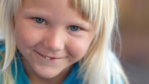 Ein Mädchen lächelt in die Kamera, ihm fehlt ein Milchzahn