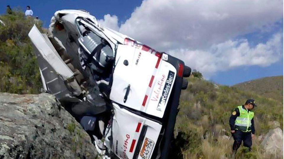 Das Foto zeigt einen Polizisten am Unfallort neben einem verunglückten Kleinbus einer Reisegruppe
