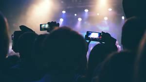 Auf einem Konzert halten Menschen ihre Smartphones in die Luft
